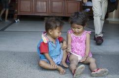 Les enfants sans abri garçon et fille du ` s de mendiant, assis, prennent soin de l'un l'autre à la cour d'église Photo stock