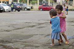 Les enfants sans abri garçon et fille du ` s de mendiant, assis, prennent soin de l'un l'autre à la cour d'église Photo libre de droits