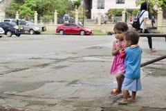 Les enfants sans abri garçon et fille du ` s de mendiant, assis, prennent soin de l'un l'autre à la cour d'église Image stock