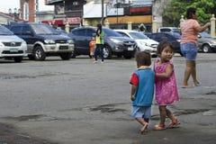 Les enfants sans abri garçon et fille du ` s de mendiant, marchant, prennent soin de l'un l'autre à la cour d'église Image stock