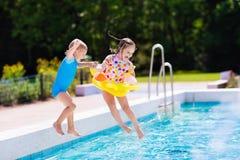 Les enfants sautant dans la piscine Image stock