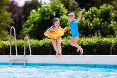 Les enfants sautant dans la piscine Photos libres de droits