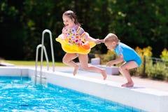 Les enfants sautant dans la piscine Images libres de droits