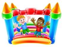 Les enfants sautant sur le château plein d'entrain Images libres de droits