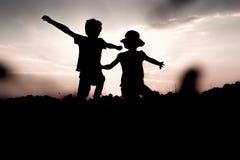 Les enfants sautent outre d'une colline soulevant des mains vers le haut de haute Photo stock