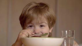 Les enfants savoureux déjeunent enfant mignon mangent B?b? mangeant de la nourriture sur la cuisine Badinez la consommation Gar?o banque de vidéos