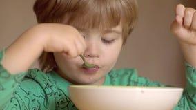 Les enfants savoureux déjeunent petit garçon s'asseyant à la table et mangeant le casse-croûte de lait Badinez la consommation Le banque de vidéos