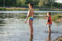 Les enfants se baignent le soir sur la plage de ville image libre de droits