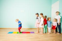 Les enfants se tiennent nu-pieds dans une rangée entre les tapis de massage image libre de droits