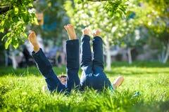 Les enfants se trouvant sur l'herbe verte en parc un jour d'été avec leurs jambes se sont soulevés jusqu'au ciel Photos stock
