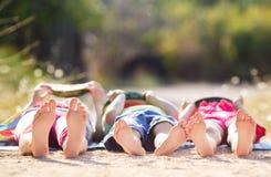 Les enfants se trouvent au sol et mangent la pastèque Photos libres de droits