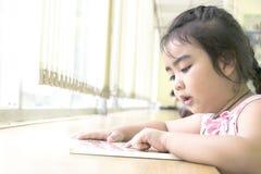 Les enfants sont des livres de lecture dans la bibliothèque Image stock