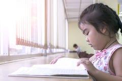 Les enfants sont des livres de lecture dans la bibliothèque Photographie stock