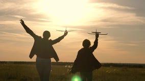 Les enfants sont lambinent sur le fond du soleil avec un avion à disposition Deux filles jouent avec l'avion de jouet au coucher  banque de vidéos