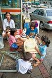 Les enfants sont les fleurs obligatoires au marché de fleur à Bangkok Photographie stock