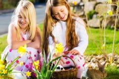 Les enfants sur l'oeuf de pâques chassent avec le lapin photo libre de droits