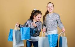 Les enfants tiennent des paquets de groupe mode de gosses Attendez plus Payez moins Amies de soeurs de filles avec le beige de sa images libres de droits