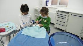 Les enfants traitent des jouets utilisant différents outils dentaires photographie stock
