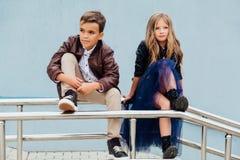 Les enfants, un garçon et une fille s'asseyent sur la balustrade dans les amis de parc Concept de l'amitié Photographie stock libre de droits