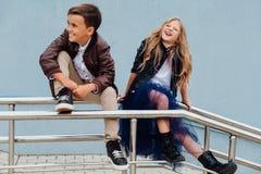 Les enfants, un garçon et une fille s'asseyent sur la balustrade dans les amis de parc Concept de l'amitié Photographie stock