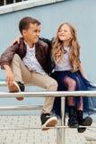 Les enfants, un garçon et une fille s'asseyent sur la balustrade dans les amis de parc Concept de l'amitié Photos stock