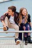 Les enfants, un garçon et une fille s'asseyent sur la balustrade dans les amis de parc Concept de l'amitié Image libre de droits