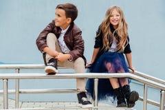 Les enfants, un garçon et une fille s'asseyent sur la balustrade dans les amis de parc Concept de l'amitié Images libres de droits