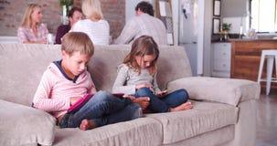 Les enfants utilisent des dispositifs de Digital pendant que les parents parlent à l'arrière-plan banque de vidéos