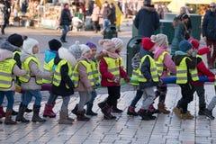 Les enfants vieillissent 6-7 ans wlaking dans une rangée sur la rue Photographie stock libre de droits