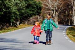 Les enfants vont à l'école - frère et soeur avec des sacs à dos marchant sur la route Photos libres de droits