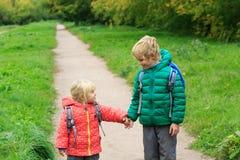 Les enfants vont à l'école - frère et soeur avec des sacs à dos sur la route Images libres de droits