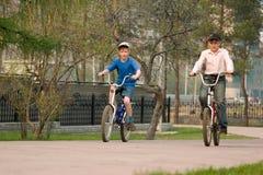 Les enfants vont chercher un lecteur sur des bicyclettes sur le stationnement. Image libre de droits