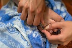 Les entretenir de fille des doigts d'ongles à la maison Nettoyez les cuticles avec des pinces de clou pour le manicur images libres de droits