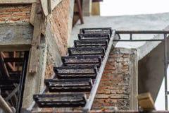 Les escaliers de fer ont placé avec des étapes modelées sur le vieux fond de brique Images libres de droits