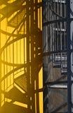 Les escaliers font quelques ombres sur un mur jaune Images libres de droits
