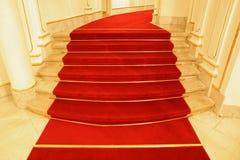 Les escaliers ont couvert le tapis rouge Photo stock