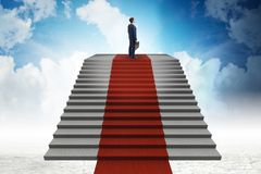 Les escaliers s'élevants de jeune homme d'affaires et le tapis rouge dans le ciel Photos stock