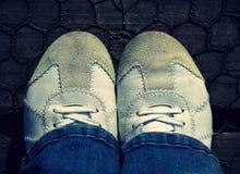 Les espadrilles blanches folâtrent les chaussures en cuir marchant sur le vieux pont de câble en bois Image stock