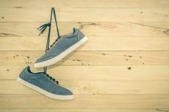 Les espadrilles bleues accrochent sur un clou sur un mur en bois brun Photos stock