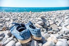 Les espadrilles bleues gauches de touristes sur la plage en pierre et sont allées nager en mer Image stock