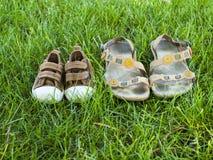 Les espadrilles de bébé et les pantoufles adultes sont sur l'herbe Image stock