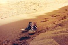 Les espadrilles de hippie en mer surfent sur un sable avec des empreintes de pas Image stock