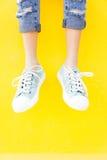 Les espadrilles de jambes sur le fond jaune, mode de mode de vie Photographie stock libre de droits