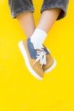 Les espadrilles de jambes sur le fond jaune, mode de mode de vie Image stock