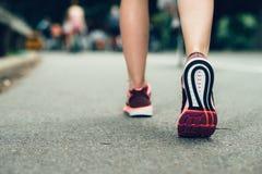 Les espadrilles de port de plan rapproché de pieds de femme pendant le marathon fonctionnent sur la route urbaine d'asphalte Photo stock