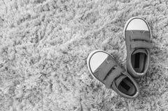 Les espadrilles de tissu de plan rapproché de l'enfant sur le tapis gris ont donné au fond une consistance rugueuse dans la vue s Images libres de droits
