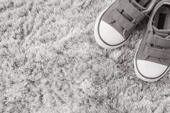 Les espadrilles de tissu de plan rapproché de l'enfant sur le tapis gris ont donné au fond une consistance rugueuse dans la vue s Photos stock