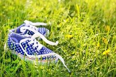 Les espadrilles des enfants américains sur le fond d'herbe verte Image libre de droits