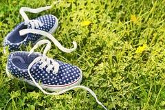 Les espadrilles des enfants américains sur le fond d'herbe verte Photographie stock