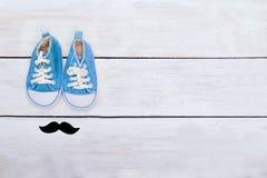 Les espadrilles et les moustaches bleues du ` s d'enfant se trouvent sur un backgr en bois blanc Photos stock